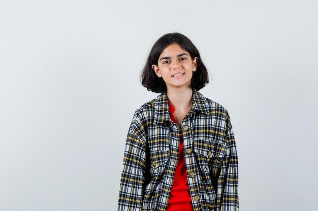 Giovane ragazza in piedi dritta e in posa alla macchina fotografica in camicia a quadri e t-shirt rossa e sembra felice. vista frontale.