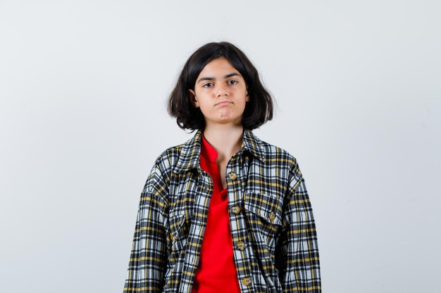 Young girl standing straight and posing at camera in checked shirt and red t-shirt and looking serious. front view.
