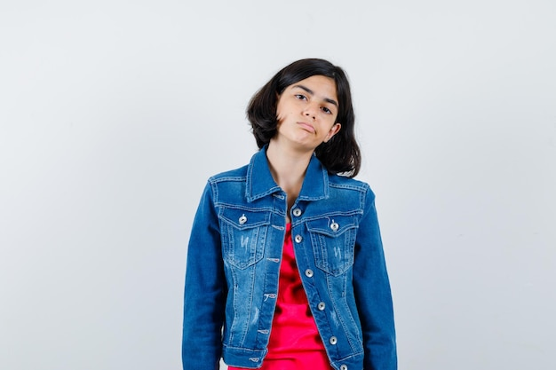 Giovane ragazza in piedi dritta e in posa alla macchina fotografica in maglietta rossa e giacca di jeans e sembra carina.