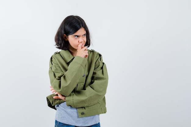 Young girl standing in thinking pose in grey sweater, khaki jacket, jean pant and looking pensive. front view.