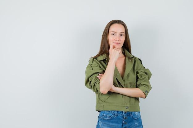 Giovane ragazza in piedi nel pensiero pongono in giacca, pantaloncini e sembra ragionevole, vista frontale.