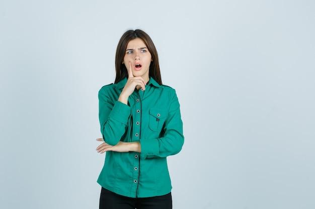 Giovane ragazza in piedi nella posa di pensiero, mettendo il dito indice vicino alla bocca in camicetta verde, pantaloni neri e guardando sorpreso. vista frontale.