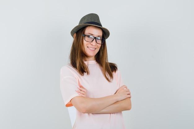 분홍색 티셔츠 모자에 교차 팔을 서서 자신감을 찾는 어린 소녀