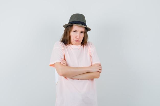 분홍색 티셔츠 모자에 교차 팔을 서서 불쾌한 찾고 어린 소녀