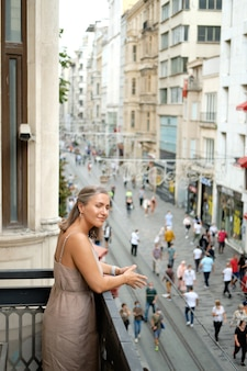 Young girl stands on the balcony against the background of the street istiklal in istanbul turkey