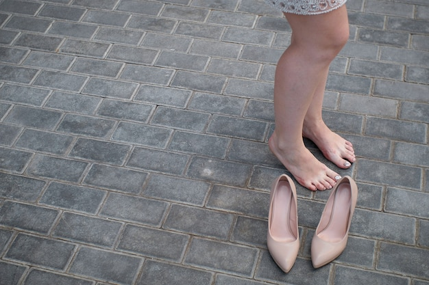 A young girl stands barefoot on the sidewalk road the woman took off her uncomfortable shoes which caused her pain and rubbed calluses