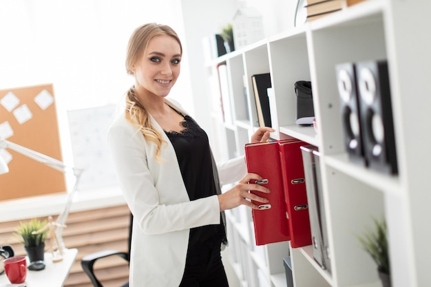 A young girl stands near a rack in the office and takes out a folder.