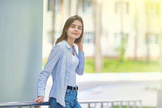 Молодая девушка стоит возле здания. скопируйте пространство.