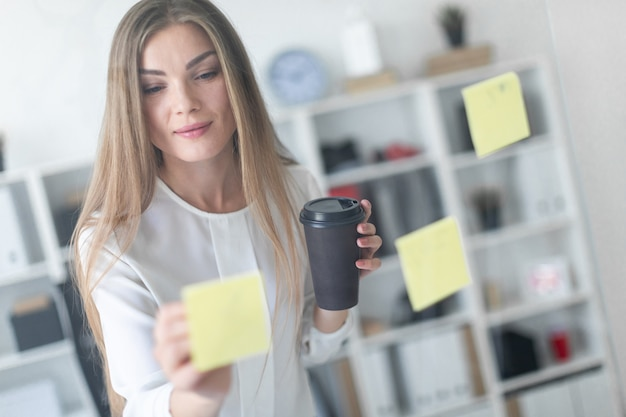 A young girl stands near a transparent board with stickers and holds a glass with coffee and a pen.
