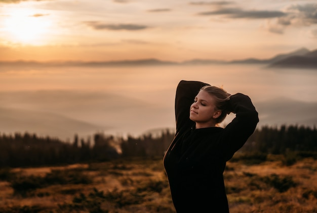A young girl stands on top of a mountain, hands behind her head and smiles in peace. side view. dawn in the mountains. the warm atmosphere of photo. inner peace. ease of mind. the balance in life.