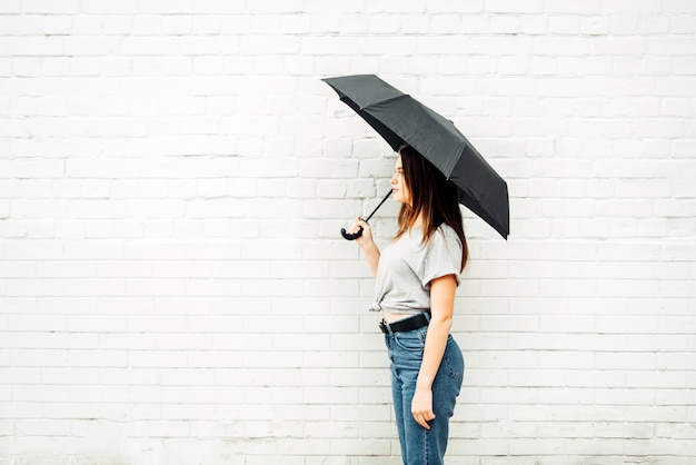 A young girl stands with a black umbrella