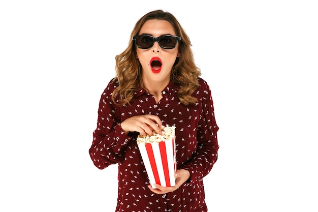 Young girl in stereo glasses holding popcorn and posing in surprise