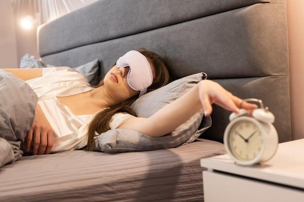 自宅のベッドに横たわっている間に目覚まし時計を停止する少女。美しい女性は目に目隠しをします。朝の目覚めの時間。モダンなアパートの寝室のインテリア