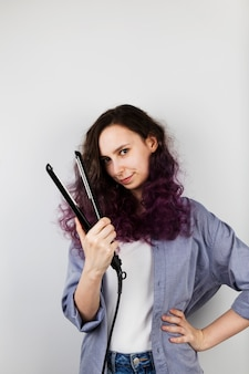Young girl straightens curly hair of flat iron. coloring purple hair. gray