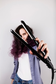 Young girl straightens curly hair of flat iron