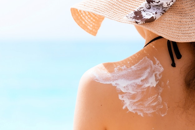 Young girl in straw hat is applying sunscreen on her back to protect her skin.