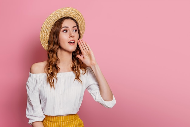Young girl in a straw hat and a white dress is shouting on a pink wall . young woman with curly hair shouting and screaming loud to the side report news web banner. sale concept