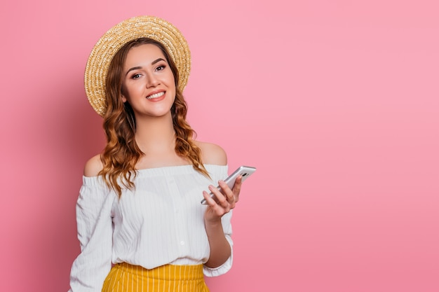 Young girl in a straw hat and a white summer dress with a mobile phone smiling on a pink wall  for text web banner. girl makes online shopping and holds smartphone in the hand