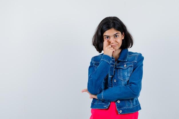 Giovane ragazza che allunga la zona degli occhi con il dito indice, sorride in maglietta rossa e giacca di jeans e sembra felice