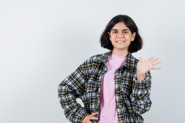 Giovane ragazza che allunga la mano mentre saluta qualcuno mentre tiene un'altra mano sulla vita in camicia a quadri e t-shirt rosa e sembra amabile. vista frontale.