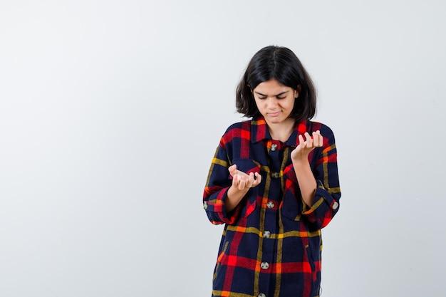 何かを持ってチェックシャツでそれを見て、焦点を合わせているように手を伸ばしている若い女の子。正面図。
