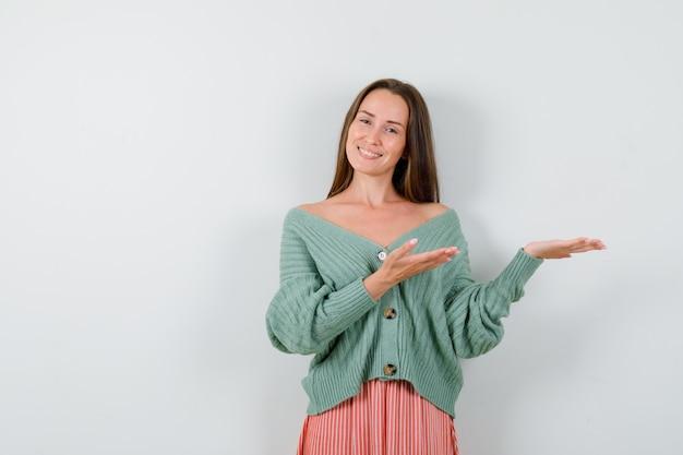 어린 소녀 니트, 치마에 상상의 뭔가를 잡고 유쾌한 찾고 손을 스트레칭. 전면보기.