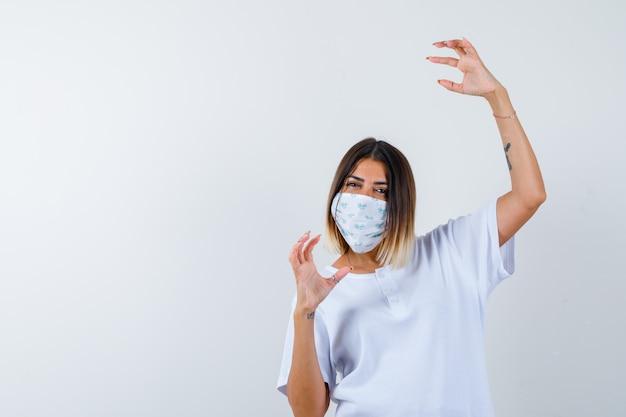 어린 소녀 흰색 티셔츠와 마스크에 상상의 뭔가를 들고 자신감을 찾고 손을 스트레칭. 전면보기.