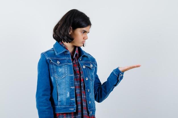 체크 셔츠와 진 재킷에 뭔가를 들고 초점을 찾고 손을 스트레칭 하는 어린 소녀. 전면보기.