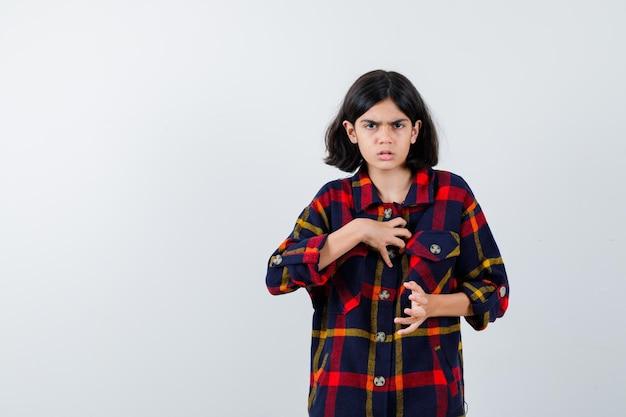 チェックのシャツに何かを持って真剣に見えるように手を伸ばす少女。正面図。