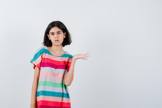 カラフルなストライプのtシャツに何かを持って驚いて見えるように手を伸ばしている少女。正面図。