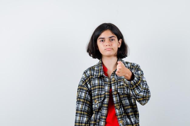 어린 소녀는 체크 셔츠와 빨간 티셔츠를 입고 진지하게 보이면서 손을 뻗고 있습니다. 전면보기.