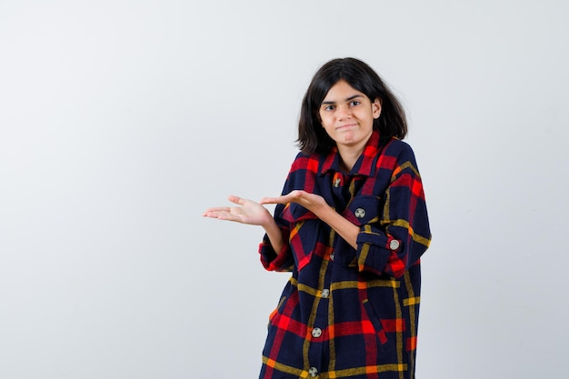 Young girl stretching hand as presenting and holding something in checked shirt and looking happy. front view.