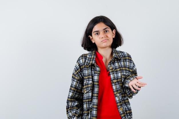 Молодая девушка вопросительно протягивает руку в клетчатой рубашке и красной футболке и выглядит сбитой с толку, вид спереди.