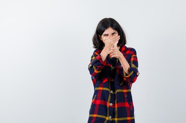 チェックシャツで顔の一部を隠すために手を伸ばして、疲れ果てているように見える少女、正面図。