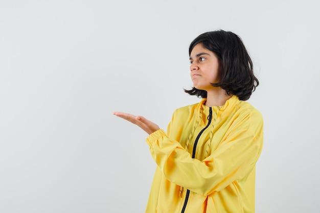 Молодая девушка в желтой куртке-бомбардировке протягивает руку влево и выглядит серьезной