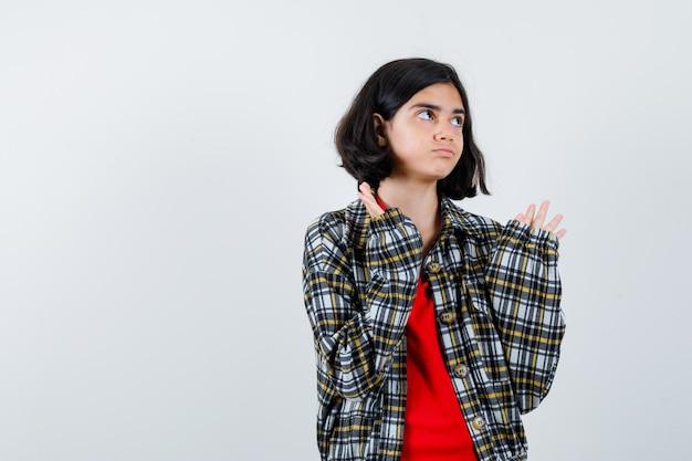 Giovane ragazza che allunga le mani mentre tiene qualcosa in camicia a quadri e maglietta rossa e sembra seria. vista frontale.