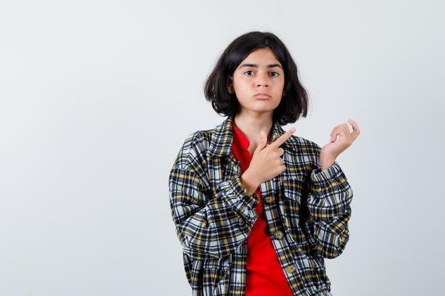 想像上の何かを持って、チェックのシャツと赤いtシャツでそれを指して、真剣に見えるように手を伸ばしている少女。正面図。