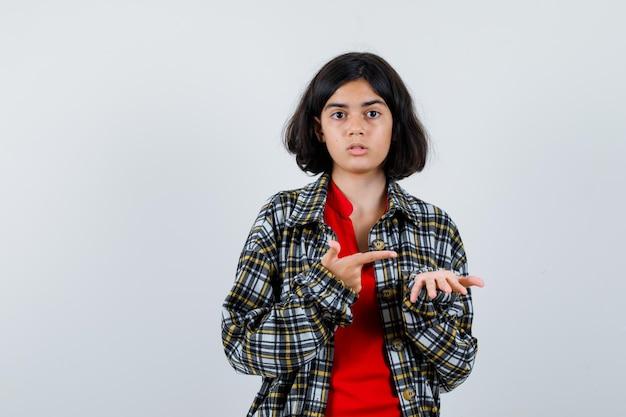 想像上の何かを持って、チェックのシャツと赤いtシャツでそれを指して、驚いて見えるように手を伸ばしている若い女の子、正面図。