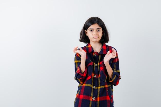 チェックのシャツに何かを持って、かわいく見えるように手を伸ばす少女、正面図。
