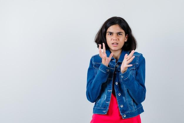 Giovane ragazza che allunga le mani mentre tiene qualcosa con una maglietta rossa e una giacca di jeans e sembra tormentata