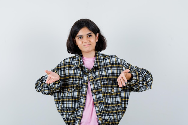 Giovane ragazza che allunga le mani invitando a venire in camicia a quadri e maglietta rosa e sembra amabile. vista frontale.