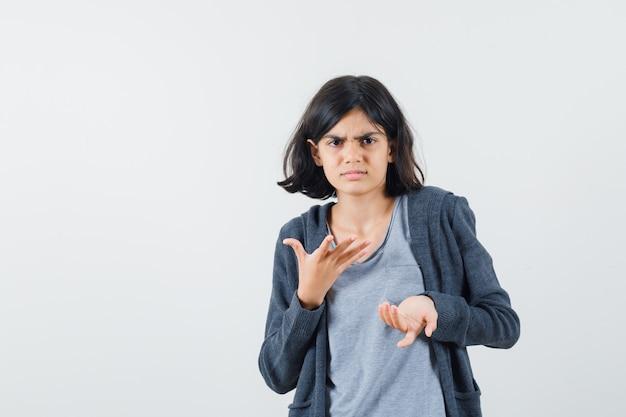 Девушка в светло-серой футболке и темно-серой толстовке на молнии с серьезным видом протягивает руки, приглашая зайти.
