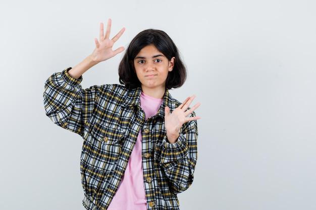 Молодая девушка протягивает руки, чтобы остановиться, в клетчатой рубашке и розовой футболке и выглядит мило.