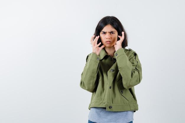 Молодая девушка сердито протягивает руки в сером свитере, куртке цвета хаки, джинсовых брюках и выглядит сердитой. передний план.