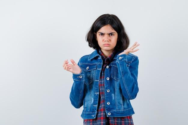 체크 셔츠와 진 재킷을 입고 질문하는 방식으로 손을 뻗은 어린 소녀와 당황한 표정.