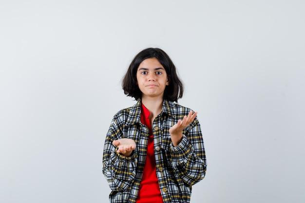 어린 소녀는 체크 셔츠와 빨간 티셔츠를 입고 질문하는 방식으로 손을 뻗고 난처한 모습을 보고 있습니다.