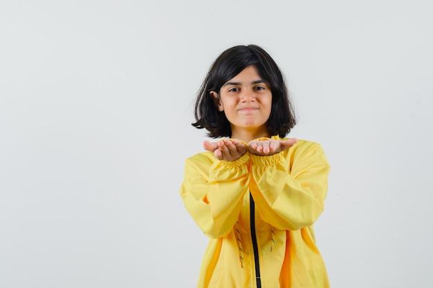 Молодая девушка протягивает руки, будто приглашает прийти в желтом бомбардировщике, и выглядит счастливой