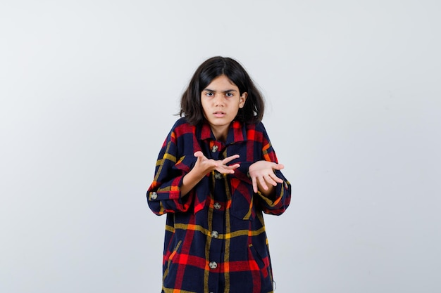 Young girl stretching hands in questioning manner in checked shirt and looking puzzled , front view.