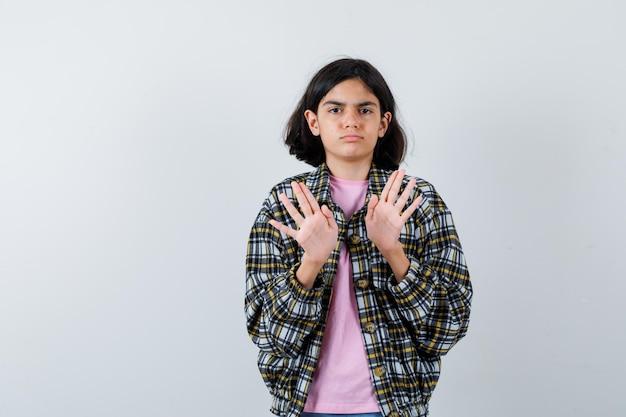 Молодая девушка протягивает руки, чтобы остановиться, в клетчатой рубашке и розовой футболке и выглядит серьезной. передний план.