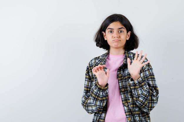 Молодая девушка протягивает руки, чтобы остановить что-то в клетчатой рубашке и розовой футболке и выглядит испуганной, вид спереди.